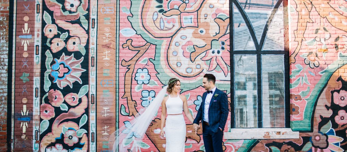 Bohemian chic bride and Groom in front of colourful wall. Caffino Ristorante Toronto