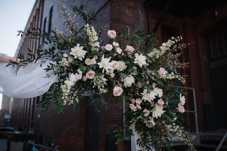 Bohemian wedding flower arrangement on wedding arch